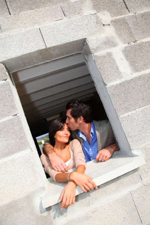 In loved couple standing in their future house photo