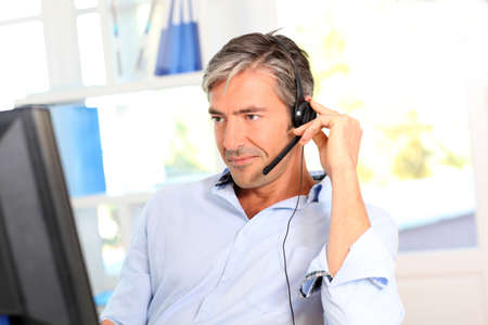 hotline: Customer service employee with headphones Stock Photo