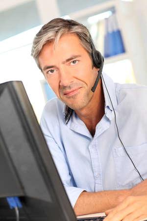 telephone salesman: Customer service employee with headphones Stock Photo