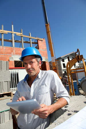 Construction manager using electronic tablet on building site Stock Photo - 10979340