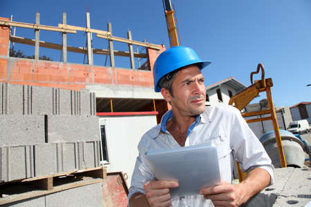Construction manager using electronic tablet on building site photo