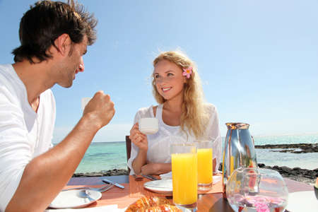 Couple having breakfast by blue lagoon Stock Photo - 11283853