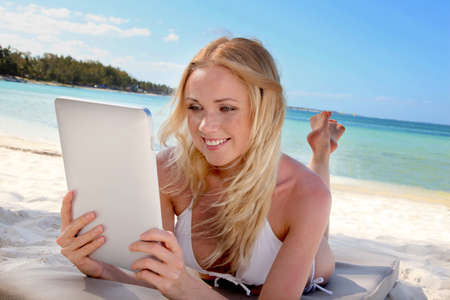 android tablet: Blond woman using electronic tablet at the beach