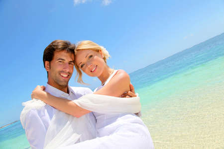 beach wedding: Groom holding bride in his arms by the sea