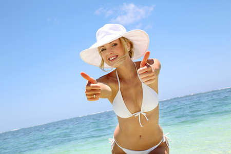 Beautiful blond woman in bikini showing thumbs up photo