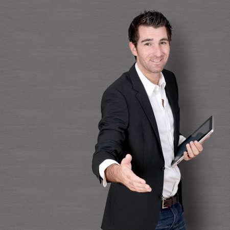 Salesman with tablet giving handshake Stock Photo - 11283815
