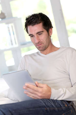 Man relaxing at home with electronic tablet photo