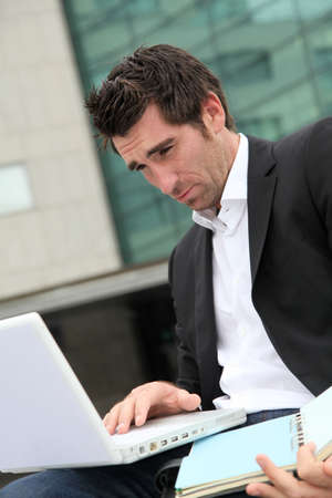 Salesman working outside building of offices photo