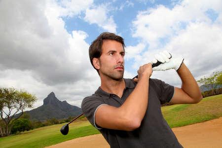 Portrait of man holding golf club photo