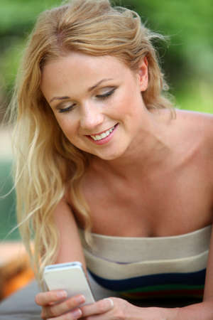 Portrait of beautiful blond woman using mobile phone photo