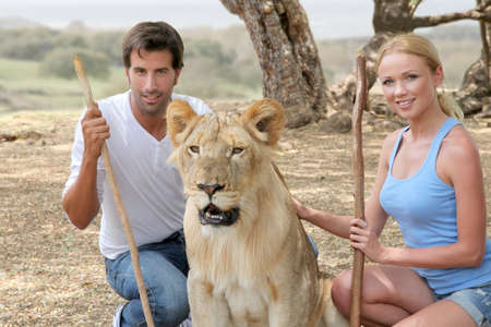 petting: Couple sitting by lion in Savannah
