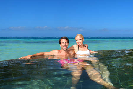 personas abrazadas: Pareja alegre relajarse en piscina del complejo