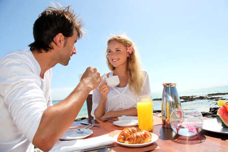 Couple having breakfast by blue lagoon photo