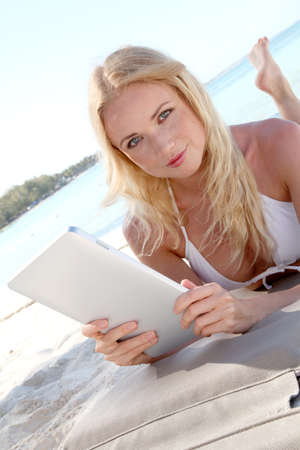 Blond woman using electronic tablet at the beach photo