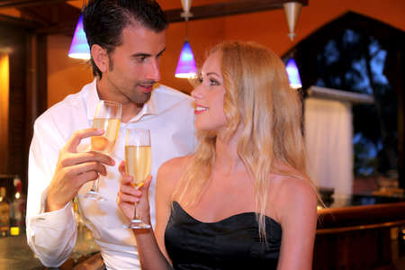 Couple drinking champagne in fancy bar photo