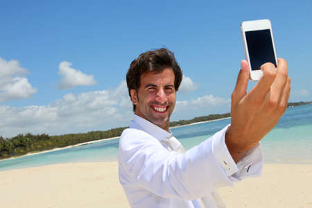 Groom taking picture of himself on a beach photo