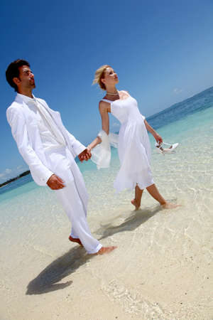 Just married couple walking on a sandy beach photo