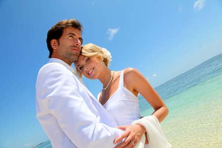 destination wedding: Bride and groom embracing by the sea Stock Photo