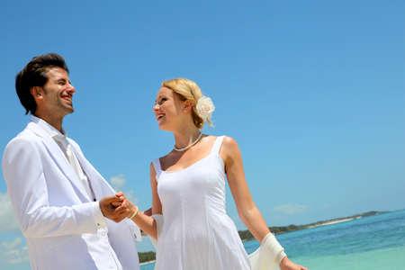 destination wedding: Bride and groom dancing by blue lagoon