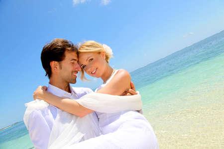 boda en la playa: El novio la celebraci�n de la novia en sus brazos al lado del mar Foto de archivo