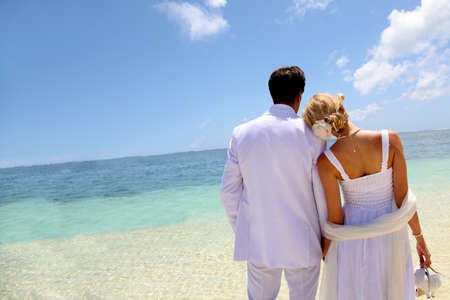 holiday destination: Just-married couple standing by blue lagoon Stock Photo
