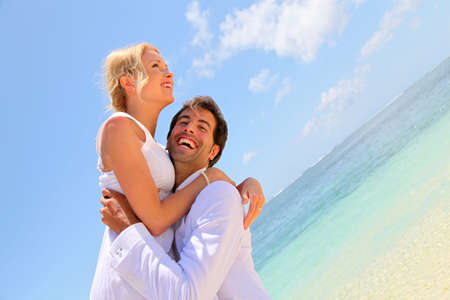 Groom and bride laughing on a sandy beach photo