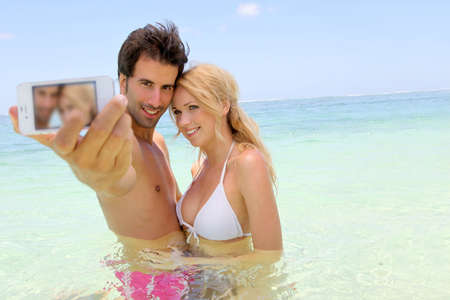guy on beach: Couple taking picture of themselves in the sea