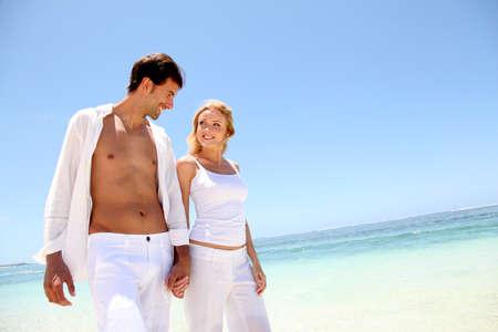 sandy: Pareja caminando por playa de arena blanca