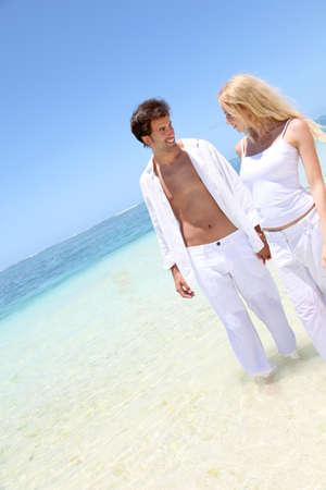 destination wedding: Couple walking on white sandy beach Stock Photo