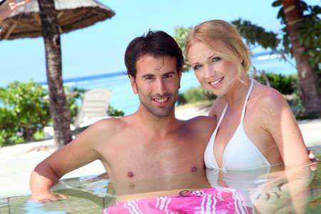 personas abrazadas: Pareja en la piscina de resort