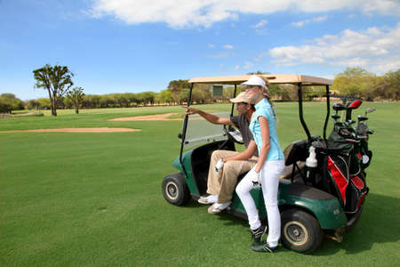 woman golf: Couple on golf course with cart