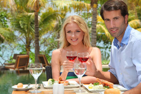 Young couple enjoying lunch in resort restaurant photo