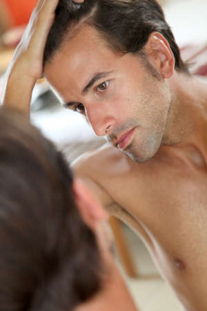 loss: Man with hair concern looking at the mirror Stock Photo