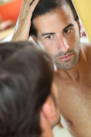 calvicie: El hombre con preocupación el pelo mirando al espejo