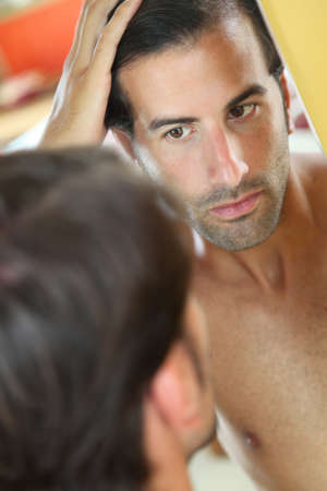 health concern: Man with hair concern looking at the mirror Stock Photo