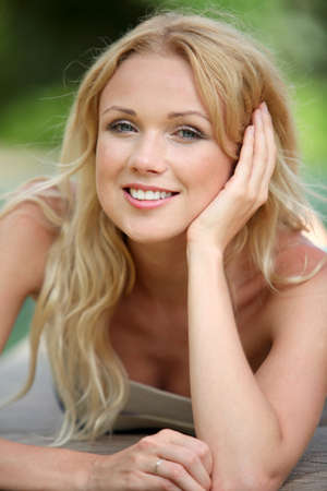 blonde yeux bleus: Portrait d'une femme belle blonde se d�tendre dans le jardin Banque d'images