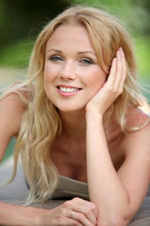 rubia ojos azules: Retrato de mujer rubia hermosa relajarse en el jard�n