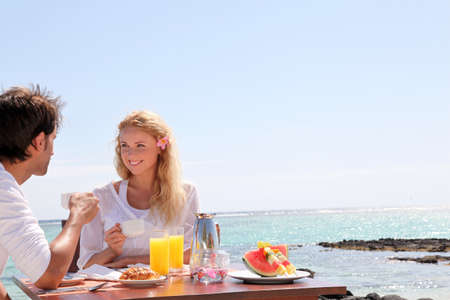 mauritius: Couple having breakfast by blue lagoon