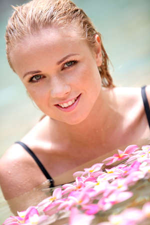 Beautiful woman bathing in pool with frangipani flowers photo