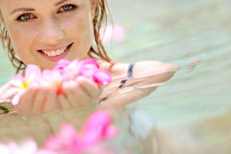thalasso: Femme qui se baignait dans la piscine avec Belle fleur de frangipanier