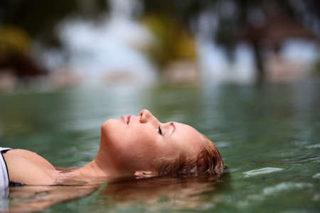 hot springs: Woman floating in swimming pool