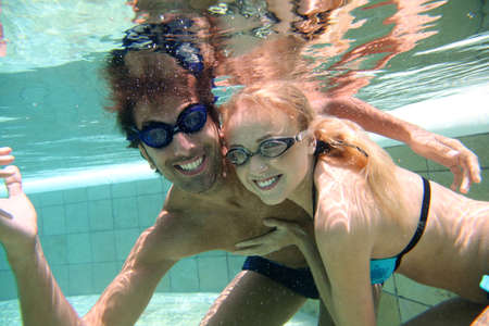 Couple swimming underwater with goggles