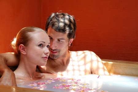 Couple relaxing in spa milk bath photo