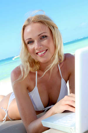 Beautiful blond woman at the beach with laptop computer photo