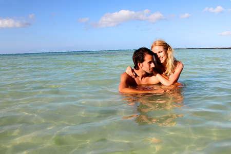personas abrazadas: Pareja que se divierte en la playa Foto de archivo