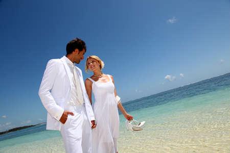 destination wedding: Just married couple walking on a sandy beach