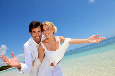 destination wedding: Married couple standing by blue lagoon Stock Photo