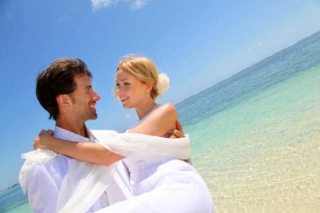 El novio la celebración de la novia en sus brazos al lado del mar