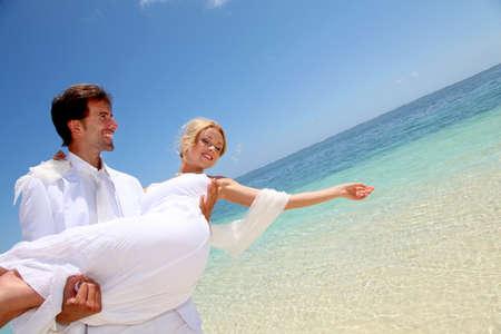 mauritius: Bruidegom die bruid in zijn armen door de zee Stockfoto