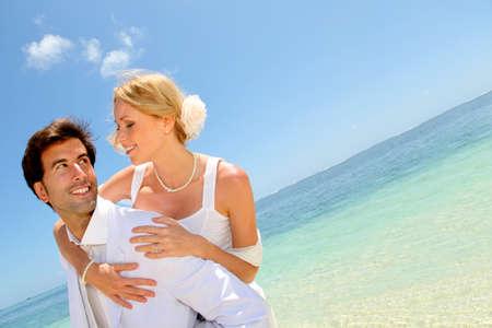 destination wedding: Groom holding bride on his back Stock Photo